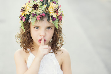 Girl (6-7) holding finger in front of mouth