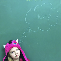 Girl (6-7) standing in front of blackboard with puzzled expression