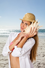Young woman listening to conch shell on the beach