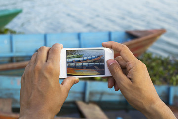 Nepal, Pokhara, Phewa Lake, Man taking photo of boats with smartphone