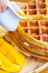 Put syrup on waffle with mango and ice cream on wooden board