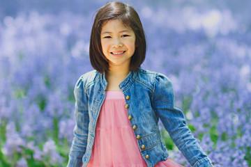Smiling girl (8-9) in bluebell field