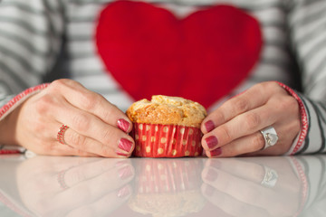 Woman with pink manicure, wearing top with big red heart, holding muffin