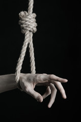 human hand hanging on rope loop on a black background