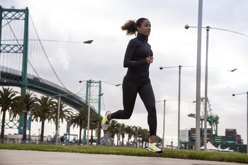 Woman running in street with bridge in background
