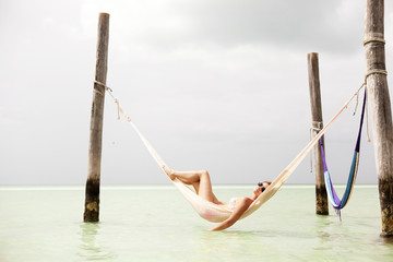 Mexico, Woman in hammock above sea