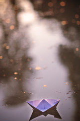 Paper boat floating on the water of a fountain with golden bokeh