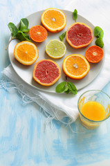 Slices of citrus fruits on plate and glass of juice
