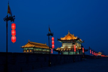 China, Shaanxi, Xian, Ancient city wall in front of traditional buildings at night