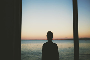 Woman looking at sea through window