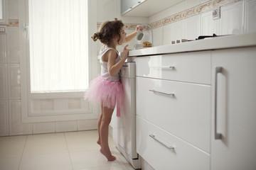 Girl (6-7) in domestic kitchen