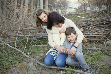 Mother playing with son (4-5) and daughter (6-7) in forest