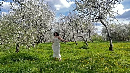 Young woman having fun in the blooming apple garden.