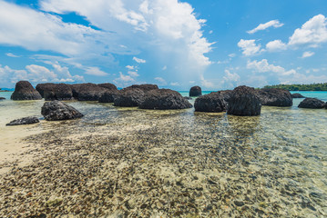 Black volcano rocks on the sand beach in the clear water