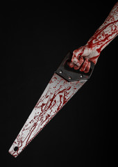 bloody hand holding a bloody saw on a black background
