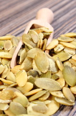 Pumpkin seeds with spoon on wooden background