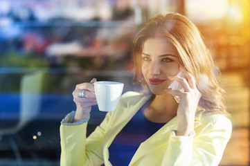 Attractive young woman with smart phone in cafe