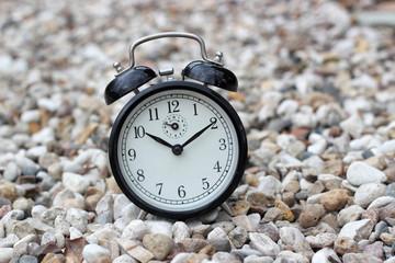Vintage alarm clock on stones