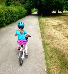 Independent girl riding bicycle, wearing a helmet and pink skirt