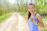 Woman drinking green smoothie wearing smartwatch