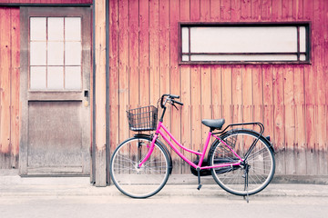 Pink bicycle and old wood walls.