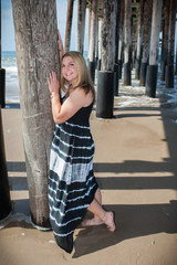 Happy teen leaning toward the pier piling