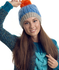 Portrait of the happy woman in a cap with a pompon