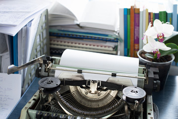 Vintage typewriter on a table with books