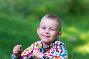 A little boy sitting on the grass and looking forward happily.