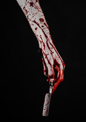 bloody hand holds a razor sharp old with a dangerous edge