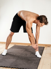 Young man doing standing leg stretches