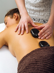 Massage therapist placing the hot stones