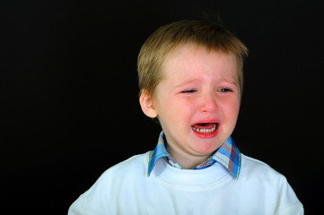 Crying little boy on a black background