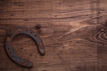 old fashioned rusted horseshoe on vintage wooden board