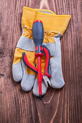 Screwdriver nippers and protective glove on wood board construct