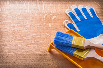 Wooden board with protective gloves paint tray and brushes const