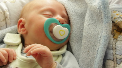 Closeup little newborn baby girl sleeping with dummy in mouth