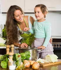 Mother with little daughter cooking at home