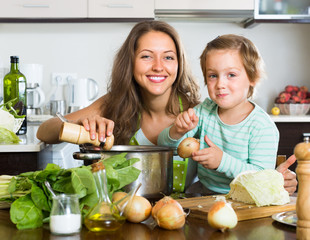 Woman with little girl cooking at home