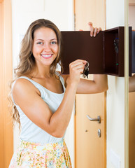 Female in casual holding appartment keys indoor
