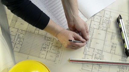 an architect while drawing adjustments in a project of a house