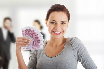 Young woman holding euro bills.