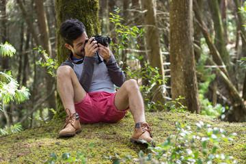 sentado tomando fotos en el bosque de frente izquierda