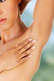 Woman touching her armpit.