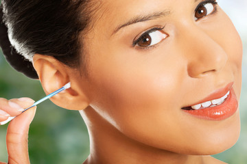 Young beauty woman is cleaning her ear.