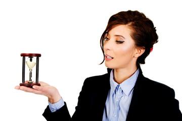 Businesswoman holding hourglass.
