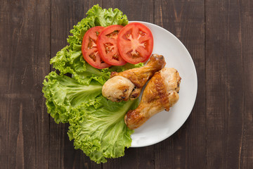 Grilled chicken legs and vegetables on wooden background.