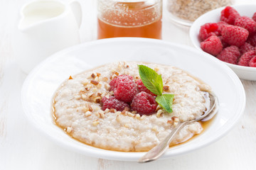 plate of oatmeal with fresh raspberries and honey, close-up