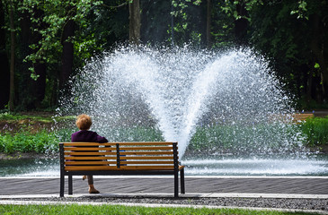 Old woman is resting on a park bench next to a fountain
