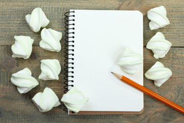 marshmallow and notepad on wooden background